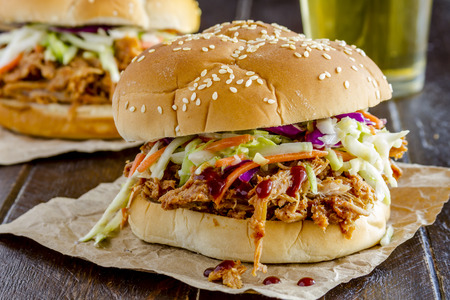 roast pork: Two pulled pork barbeque sandwiches with coleslaw sitting on wooden table with glass of beer