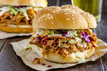 Close up of pulled pork barbeque sandwich with coleslaw sitting on wooden table with glass of beer