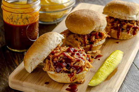 Three pulled pork barbeque sliders sitting on wooden cutting board with dill pickle with bottle of sauce and bowl of potato chips