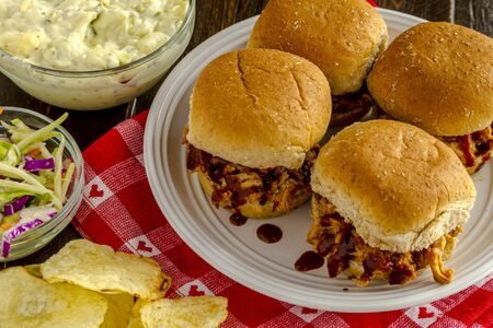 sliders: Four pulled pork barbeque sliders sitting on white plate with potato chips, coleslaw and potato salad on red heart napkin