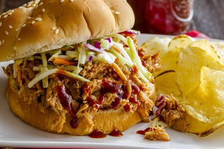 sliders: Large pulled pork barbeque sandwich with coleslaw sitting on white plate with potato chips on the side