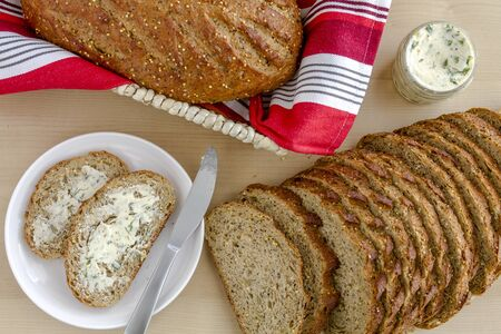 whole grains: Whole grains and seeds fresh baked bread with herb butter from above Stock Photo