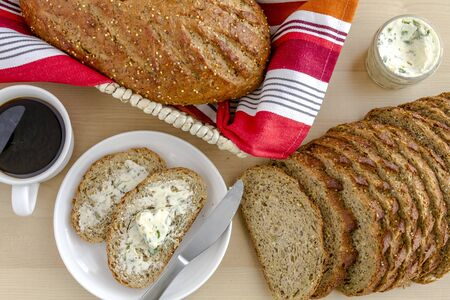 whole grains: Whole grains and seeds fresh baked bread with herb butter and cup of coffee from above Stock Photo