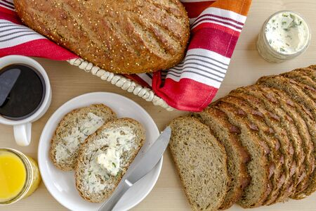 whole grains: Whole grains and seeds fresh baked bread with herb butter, cup of coffee and orange juice from above