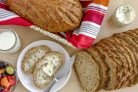 whole grains: Whole grains and seeds fresh baked bread with herb butter, fruit and glass of milk from above