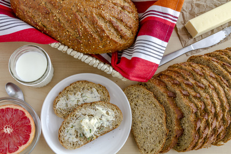 whole grains: Whole grains and seeds fresh baked bread with herb butter, grapefruit and glass of milk from above Stock Photo