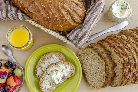 whole grains: Whole grains and seeds fresh baked bread with herb butter sitting on green plate, fruit and glass of orange juice from above