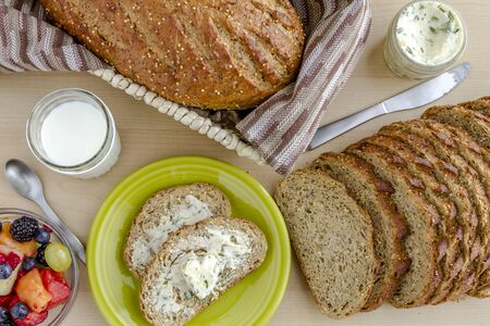 whole grains: Whole grains and seeds fresh baked bread with herb butter sitting on green plate, fruit and glass of milk from above Stock Photo