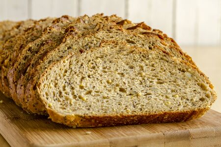 Slices of whole grain and seeds fresh baked bread sitting on wooden cutting board