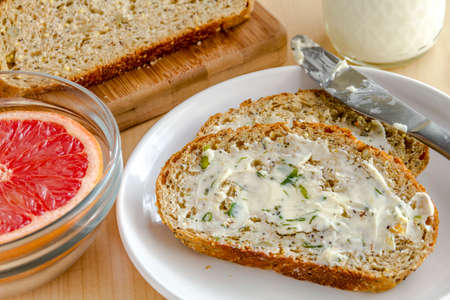 Close up of slices of whole grain and seeds fresh baked bread with herb butter sitting on white plate with glass of milk and grapefruit