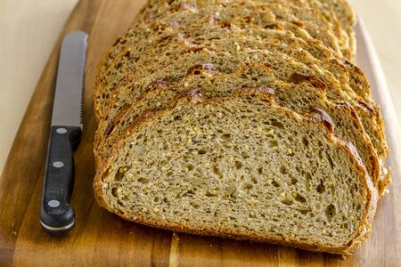 Slices of whole grain and seeds fresh baked bread sitting on wooden cutting board with knife