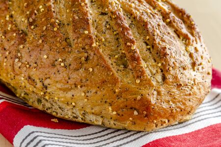 Close up of loaf of whole grain and seeds fresh baked bread sitting on orange striped towel