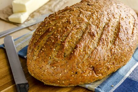 Loaf of whole grain and seeds fresh baked bread sitting on blue triped towel with butter and knife Stockfoto
