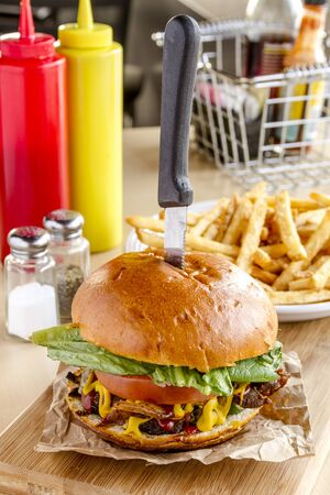 Gourmet pub hamburger with bacon on wooden cutting board with plate of french fries sitting on wooden table Stock Photo - 37228534