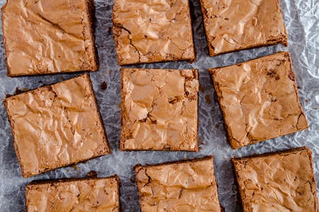 semisweet: Close up of homemade double chocolate chunk brownies sitting on parchment paper Stock Photo