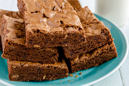 semisweet: Homemade double chocolate chunk brownies sitting on bright blue plate Stock Photo