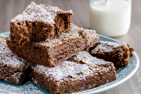 Stack of homemade double chocolate chunk brownies dusted with powdered sugar sitting on bright blue plate with glass of milk photo