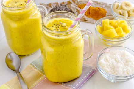 noix de coco: Smoothies aux fruits frais m�lang�s � base d'ananas, banane, noix de coco, le curcuma et graines de chia entour�es de mati�res premi�res rose pailles