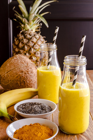 Fresh blended fruit smoothies made with pineapple, banana, coconut, turmeric and chia seeds surrounded by raw ingredients in glass milk bottles with black and white straws