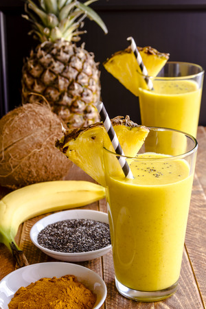 swirled: Fresh blended fruit smoothies made with pineapple, banana, coconut, turmeric and chia seeds surrounded by raw ingredients in drinking glass with pineapple slice garnish and blue swirled straw Stock Photo