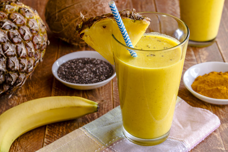 Close up fresh blended fruit smoothies made with pineapple, banana, coconut, turmeric and chia seeds surrounded by raw ingredients in drinking glass with pineapple slice garnish and blue striped straw