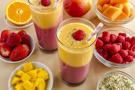 mango: Fresh blended fruit smoothies made with mango, orange, cantaloupe, raspberries, strawberries and hemp seeds surrounded by raw ingredients with pink swirled straws