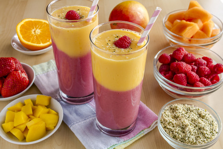 Fresh blended fruit smoothies made with mango, orange, cantaloupe, raspberries, strawberries and hemp seeds surrounded by raw ingredients with pink swirled straws and pastel napkin Stockfoto