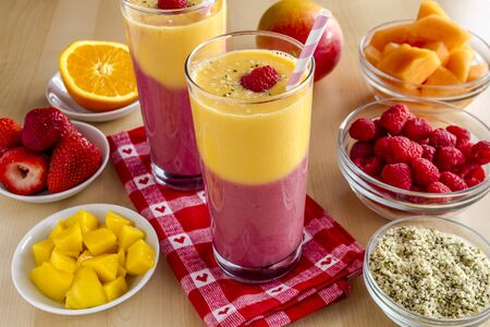 swirled: Fresh blended fruit smoothies made with mango, orange, cantaloupe, raspberries, strawberries and hemp seeds surrounded by raw ingredients with pink swirled straws and red heart napkin
