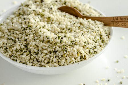 Organic hemp seeds in white bowl with measuring spoon on white background