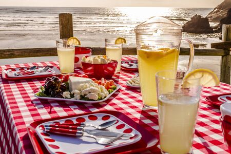 close up food: Close up of picnic at the beach overlooking the ocean at sunset with table set with food, dishes, glasses and red checkered table cloth