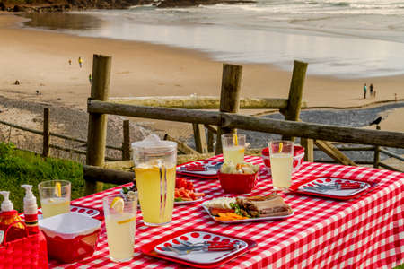 close up food: Close up of picnic at the beach overlooking the ocean with haystack rocks at sunset with table set with food, dishes, glasses and red checkered table cloth