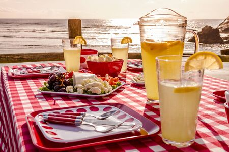 Close up of picnic at the beach overlooking the ocean at sunset with table set with food, dishes, glasses and red checkered table cloth photo
