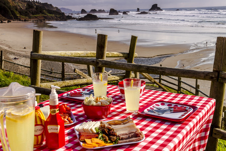 Close up of picnic for 2 at the beach overlooking the ocean with haystack rocks at sunset with table set with food, dishes, glasses and red checkered table cloth