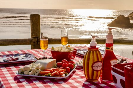 close up food: Close up of picnic for 2 at the beach overlooking the ocean with haystack rocks at sunset with table set with food, dishes, wine glasses filled with wine and red checkered table cloth