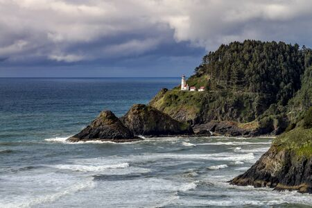 Historic Heceta Head lighthouse sitting on scenic headland cliffs along Oregon's central coast on a stormy afternoon. A popular tourist attraction and landmark photo