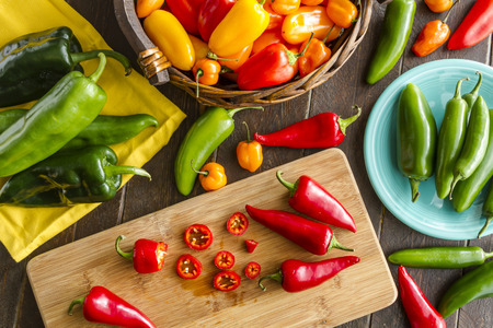 Assorted colorful varieties of hot and sweet peppers sitting on table with cutting board, yellowe napkin and blue plate