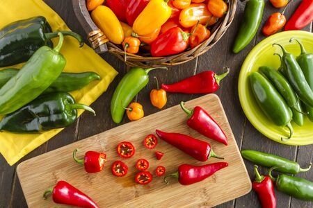 sweet peppers: Assorted colorful varieties of hot and sweet peppers sitting on table with cutting board, yellow napkin and green plate