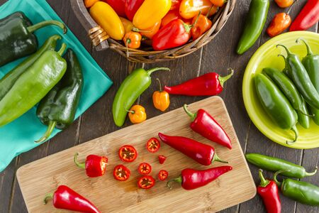 sweet peppers: Assorted colorful varieties of hot and sweet peppers sitting on table with cutting board, blue napkin and green plate Stock Photo