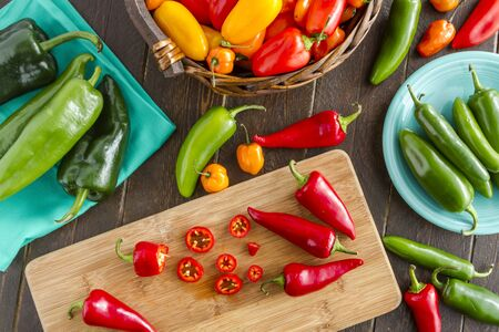sweet peppers: Assorted colorful varieties of hot and sweet peppers sitting on table with cutting board, blue napkin and blue plate Stock Photo