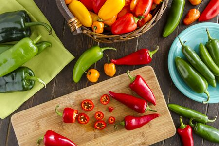 sweet peppers: Assorted colorful varieties of hot and sweet peppers sitting on table with cutting board, green napkin and blue plate Stock Photo