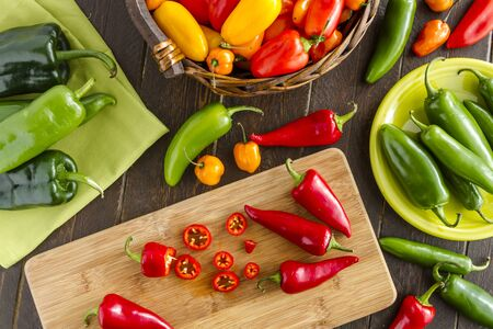 sweet peppers: Assorted colorful varieties of hot and sweet peppers sitting on table with cutting board, green napkin and plate