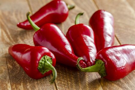 Red fresno peppers sitting on wooden table Stock Photo