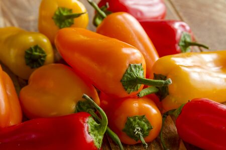 sweet peppers: Pile of assorted colors of sweet peppers sitting on wooden table Stock Photo