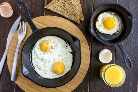 whole wheat toast: Fried eggs in cast iron skillet sitting on kitchen table with whole wheat toast and orange juice
