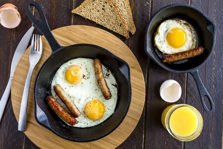 whole wheat toast: Fried eggs and sausage links in cast iron skillet sitting on kitchen table with whole wheat toast and orange juice