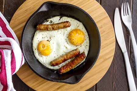 cast iron red: Fried eggs and sausage links in cast iron skillet sitting on kitchen table with red striped napkin