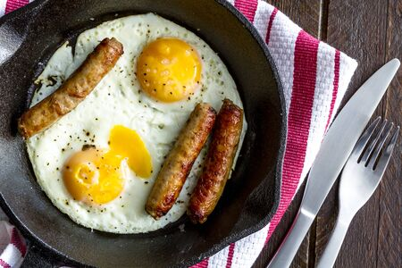 cast iron red: Close up of fried eggs and sausage links in cast iron skillet sitting on kitchen table with red striped napkin