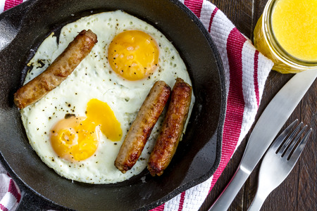 cast iron red: Close up of fried eggs and sausage links in cast iron skillet sitting on kitchen table with orange juice and red striped napkin Stock Photo