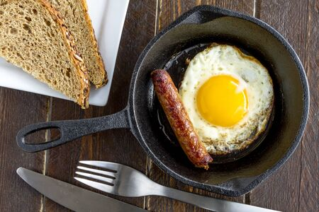wheat toast: Single fried egg and sausage link in cast iron skillet sitting on wooden kitchen table with whole wheat toast slices