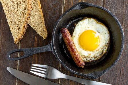 whole wheat toast: Single fried egg and sausage link in cast iron skillet sitting on wooden kitchen table with whole wheat toast slices